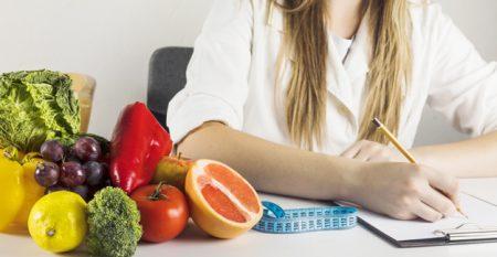 foto mano-dietista-que-escribe-tablero-comida-sana-escritorio_23-2147882179